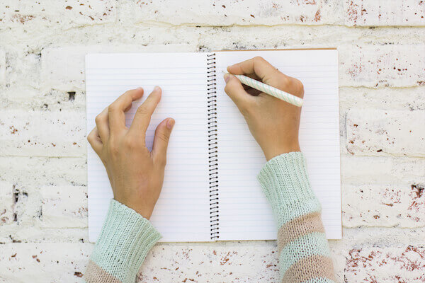 woman journaling in notepad